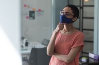 Mixed race woman wearing mask in an office