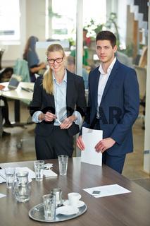 Zwei Geschäftsleute stehen im Konferenzraum