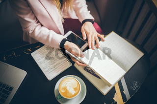 Woman freelancer leafing through pages of a diary in a coffee shop. Entrepreneur working in cafe. Business woman uses paper reminders and schedules. Girl writes notes diary, makes business plan