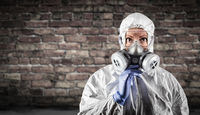 Woman Wearing Hazmat Suit, Protective Gas Mask and Goggles Against Brick Wall