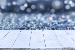 Empty white wooden boards or table top over blue bokeh blurred background. Template, mockup for display or montage of products. Close up, copy space