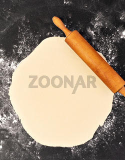 Preparation of the dough. The rolling pin with flour on a dark background