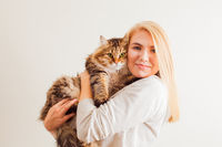 Beautiful woman holding new adopted fluffy cat with green eyes