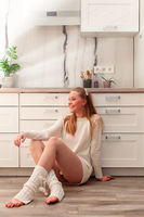 Woman in white sweater and stockings, sitting on a floor