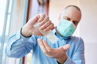 Senior in Quarantäne beim Hände desinfizieren