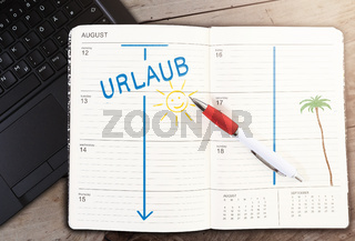 calendar on table with word URLAUB, German for vacation, and sun icon against wooden table