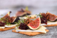 Cracker with a slice of camembert, jam, figs and nuts. A great snack idea for a holiday, picnic or p