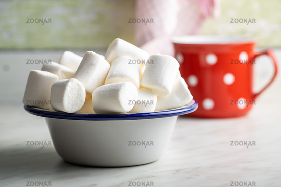 White sweet marshmallows candy in bowl on kitchen table.