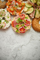 Homemade Bagel sandwiches with different toppings, salmon, cottage cheese, hummus, ham, radish