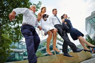 Geschäftsleute springen über Hindernis