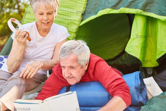 Senioren Paar beim Buch lesen vor dem Zelt