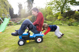 A young boy pushing a man on a toy tractor