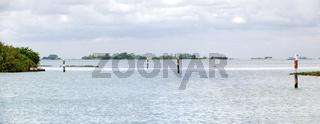 Lagune von Grado mit Pfählen zur Markierung der Schifffahrtsrinne