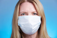 Blonde woman wearing a respiratory face mask. Medical safety, research and corona virus concept.