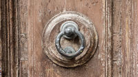 Old handle on a brown wooden door