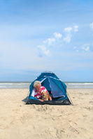 Man with dog camping in shelter at the beach
