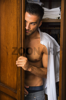 Sexy handsome young man peering out of a closet