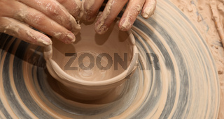 Woman in process of making clay bowl on pottery wheel
