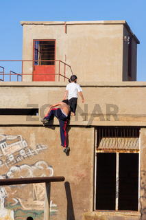 Two boys are climbing on the roof of an abandoned buildiing in Argaka in Cyprus.