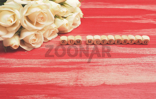 Bouquet of white roses on a red wooden table German Mother's Day
