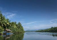 boat and jungle hut on the tatai river in cambodia