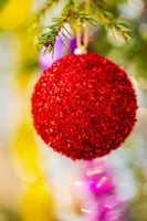 Close-up view of bright red Christmas ball and shining tinsel hanging on branch of tree. Xmas festive composition for Happy New Year