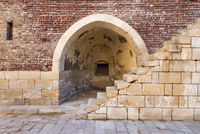 Ancient brick building with shabby stone stairway and crumbling arched alcove