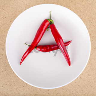Fresh chili peppers on plate arranged in A letter shape