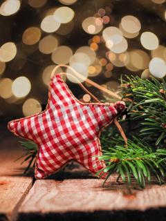 Homemade cloth star with fir branches on a wooden table in front of a Christmas tree bokeh.