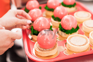 the confectioner decorates a beautiful French mousse dessert