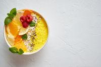 Tasty orange fresh smoothie or yogurt served in bowl. With raspberries, orange slices, chia seeds