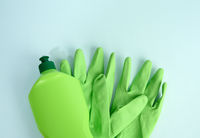 green rubber gloves for cleanin and cleaning fluid in a plastic bottle