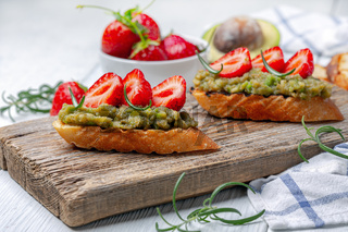 Baguette slices with avocado puree and strawberries.