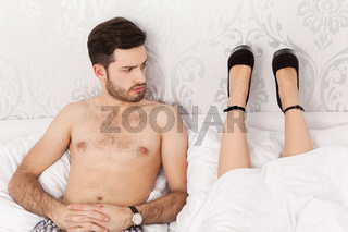 Man in bed wondering about the lying position of his girlfriend