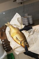 Smoked mackerel in hands in a warehouse.