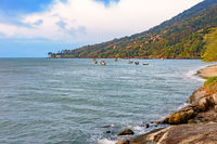 Beach with tropical vegetation and boats over the sea in Ilhabela island
