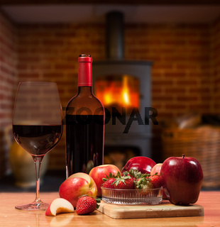Red wine and fruit in front of burning fire
