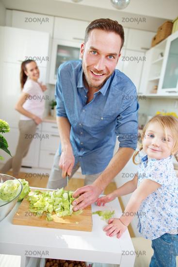 Vater schneidet Salat mit Messer