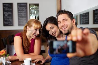 Gruppe macht Handyfotos im Café