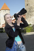 The smiling woman with the camera photographs old city wall towers. Tallinn, Estonia