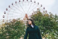 Young adult asian female in a dark coat in front of ferris wheel outdoors