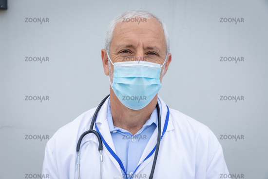 Portrait of senior male doctor wearing face mask  against grey background