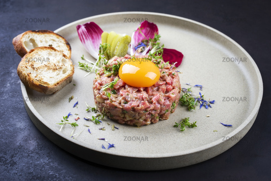 Gourmet tartar raw from beef fillet with yellow of the egg grilled and baguette as closeup on modern design dish