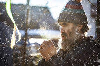 An elderly man with a beard in a knitted hat warms his hands in the cold.