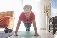 Senior woman doing fitness training with eyes closed.