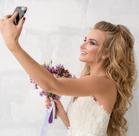 Young bride with bouquet in studio making selfie