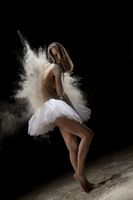 Slim girl in tutu in white dust cloud view