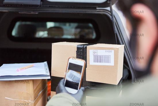Paketbote scannt Barcode mit Smartphone von Paket