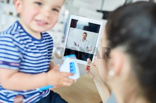 Mutter mit Kind im Videochat mit einem Kinderarzt