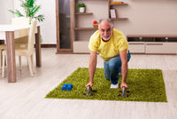 Aged man doing sport exercises at home